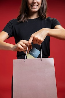 Front view woman putting credit card in shopping bag