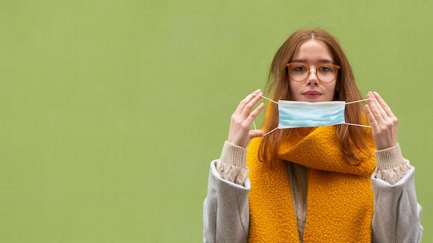 Vista frontale della donna che indossa la mascherina medica con lo spazio della copia