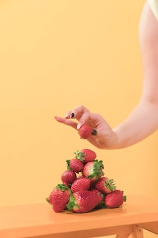 Front view of woman putting strawberry on top of pile