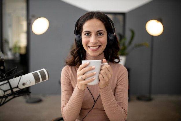 Front view of woman in a radio studio with microphone and coffee
