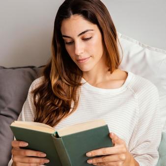 Vista frontale della donna che legge un libro a casa