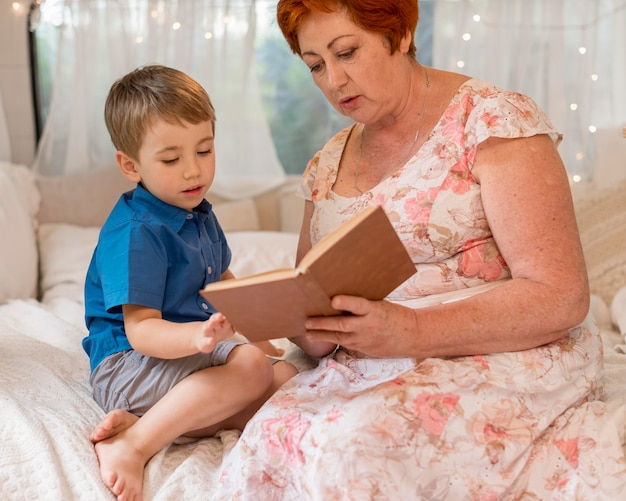 Front view woman reading to her grandson in a caravan