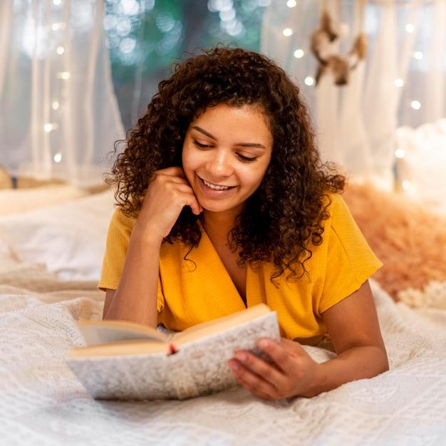 Вид спереди женщина, читающая в помещении