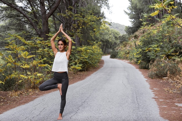 Front view of woman on the road doing yoga with copy space