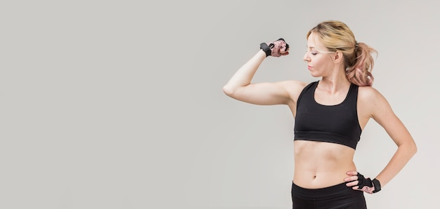 Front view of woman showing her bicep with copy space
