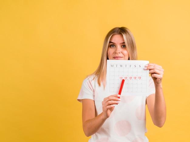 Donna di vista frontale che mostra il suo calendario mestruale con una penna