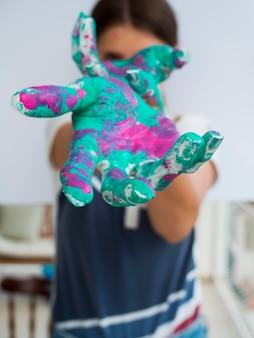 Vista frontale della donna che mostra le mani dipinte