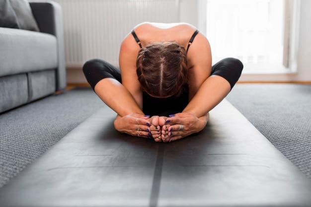 Вид спереди женщина сидит и растягивается на коврике для йоги