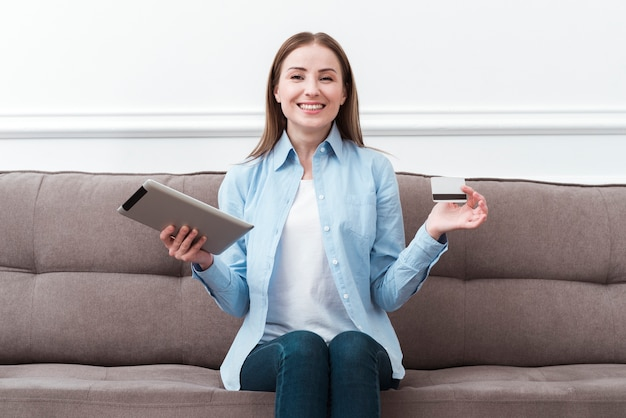 Front view woman sitting on couch with digital tablet and credit card