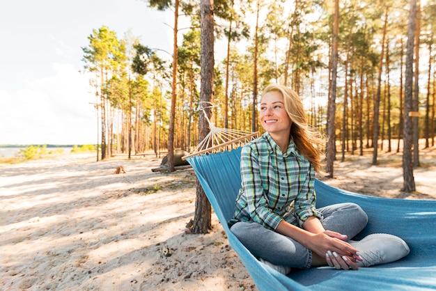 Donna di vista frontale che si siede in amaca e distoglie lo sguardo