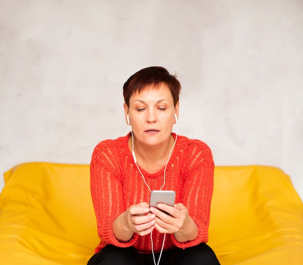 Front view woman sitting o sofa and listening music