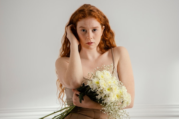 Front view of woman sitting and posing with spring flowers