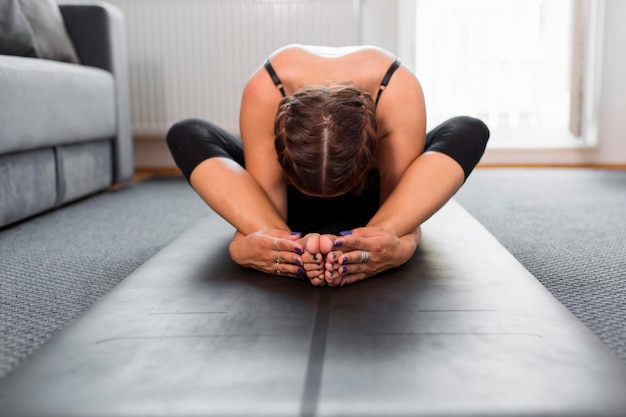 Front view woman sitting and stretching on yoga mat