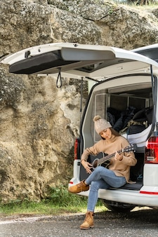 Front view of woman sitting in the trunk of the car while on a road trip and playing guitar