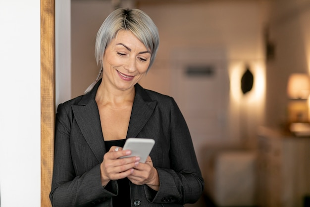 Женщина вид спереди улыбается во время lookinf на телефон