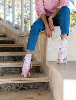 Front view of woman on stairs posing with roller skates