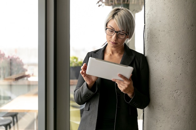 Front view woman standing and holding tablet