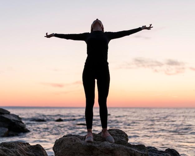 海の隣の岩の上に立っている正面図の女性