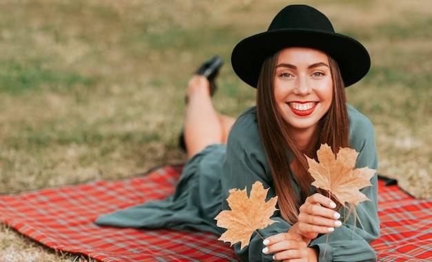 Вид спереди женщина, стоящая на одеяле, держа в руках сухие листья с копией пространства