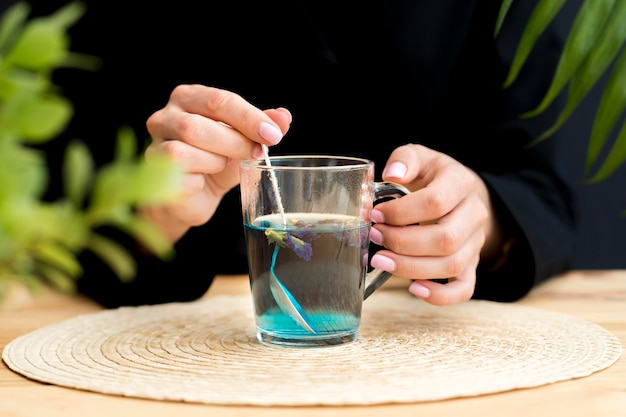 Front view woman stirring blue tea in glass