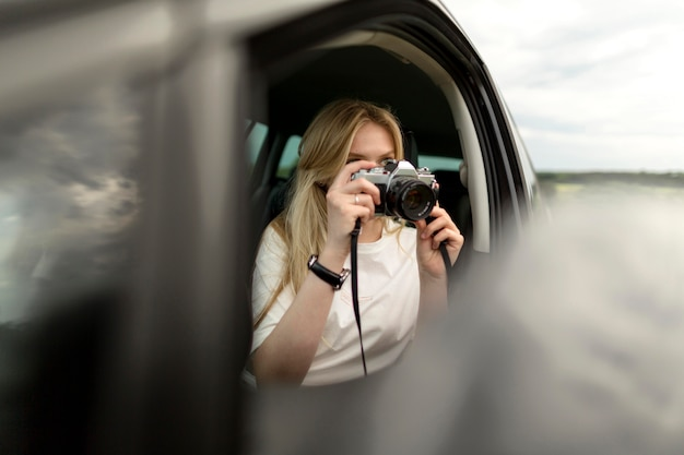 Front view of woman taking pictures with camera from car