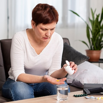 Front view of woman taking pills