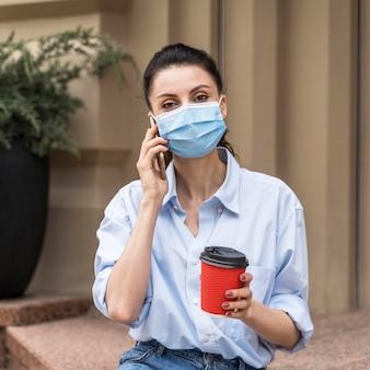 医療用マスクをつけたまま電話で話している正面図の女性