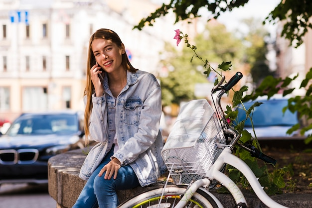 Front view woman talking on phone next to bike