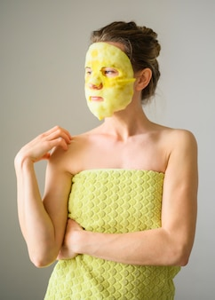 Front view of woman in towel with face mask