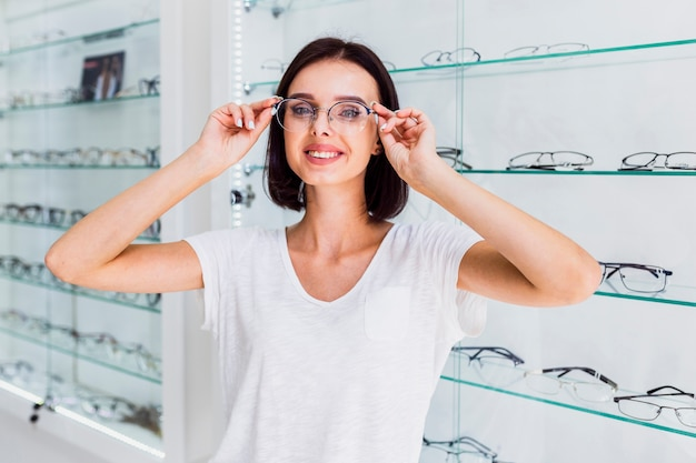 Front view of woman trying on glasses frame