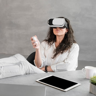 Front view woman trying a vr set and holding a remote