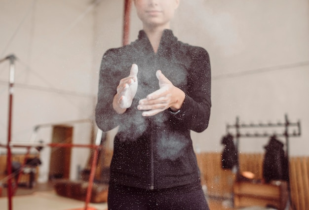 Front view woman using chalk for gymnastics training