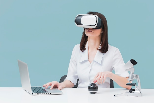 Front view of woman using laptop and virtual reality headset