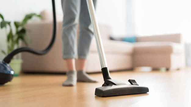 Front view of woman using vacuum cleaner in room