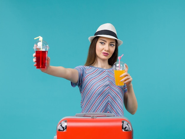 Front view woman in vacation holding fresh drinks on the blue background sea plane voyage summer journey