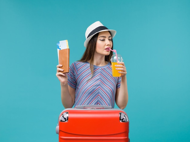Front view woman in vacation holding fresh juice and tickets on blue background trip journey voyage vacation sea summer