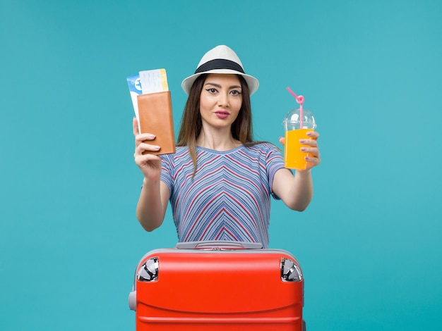 Front view woman in vacation holding fresh juice and tickets on blue desk trip summer journey voyage vacation sea