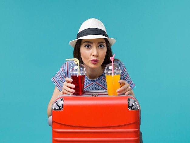 Front view woman in vacation holding fresh juices on blue background sea plane journey voyage summer