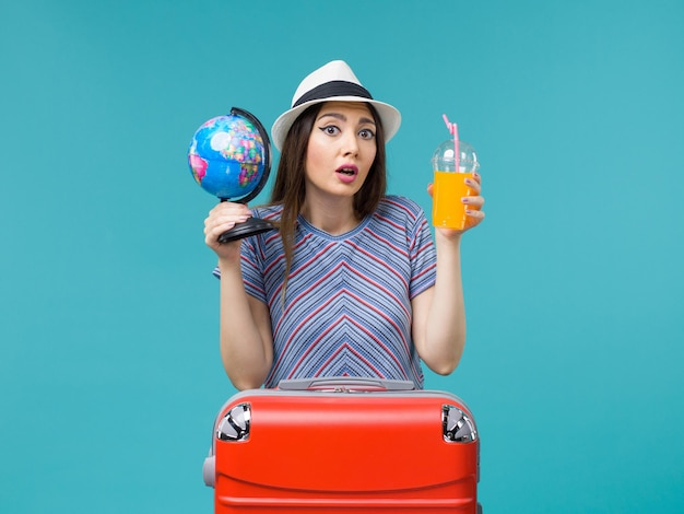Front view woman in vacation holding juice and globe on blue background sea trip voyage vacation summer journey