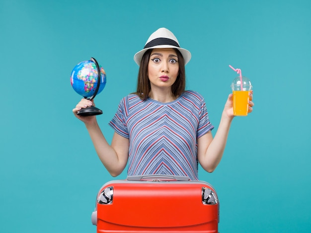 Front view woman in vacation holding juice and globe on blue background sea voyage summer trip journey vacation
