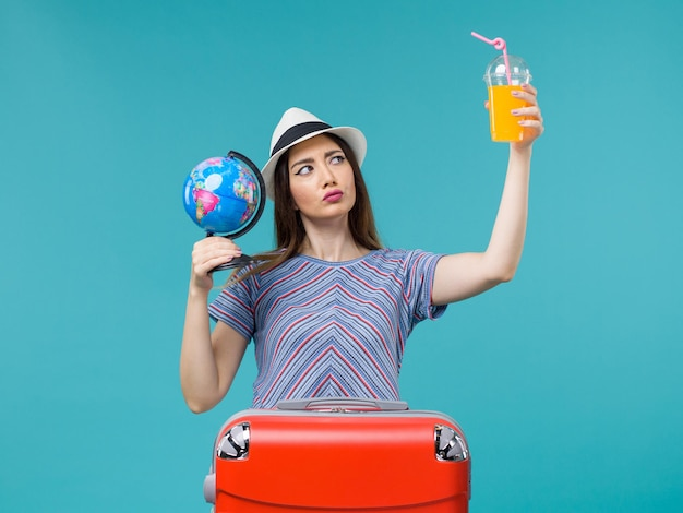 Front view woman in vacation holding juice and globe on blue desk sea trip voyage vacation summer journey
