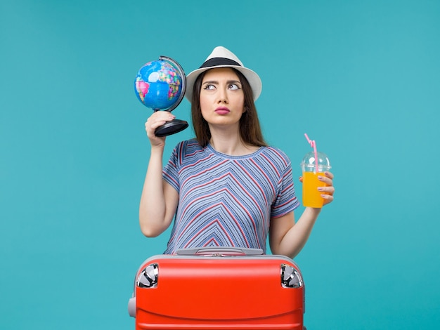 Front view woman in vacation holding juice and globe on light blue background sea voyage vacation summer trip journey