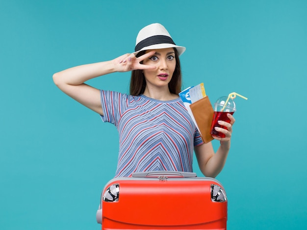 Front view woman in vacation holding juice with tickets on blue desk voyage journey female sea summer plane