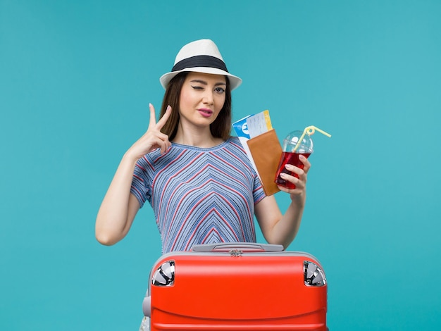Front view woman in vacation holding juice with tickets on light-blue background voyage journey female sea summer plane