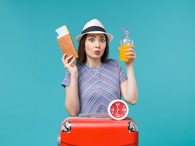 Front view woman in vacation holding tickets and juice on blue desk voyage vacation sea trip journey female