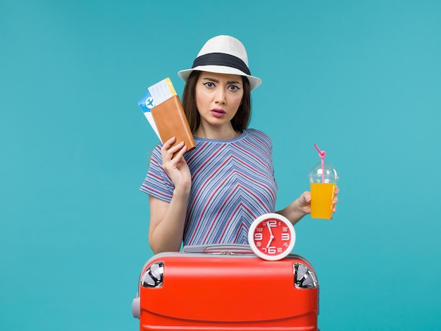 Front view woman in vacation holding tickets and juice on light-blue background voyage vacation sea trip journey female