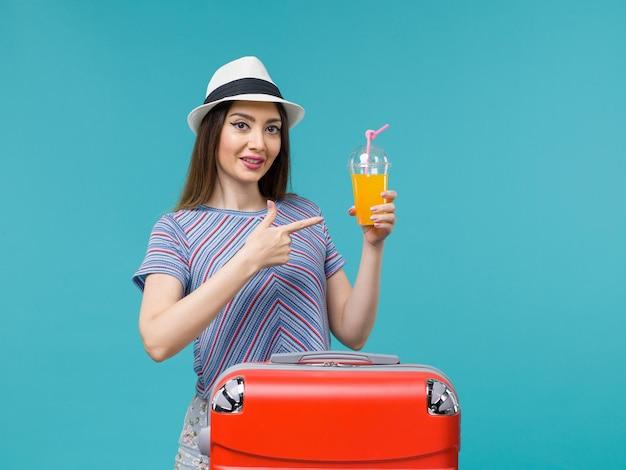 Donna di vista frontale in vacanza con la sua borsa rossa che tiene il suo succo sullo sfondo blu viaggio viaggio vacanza viaggio femminile