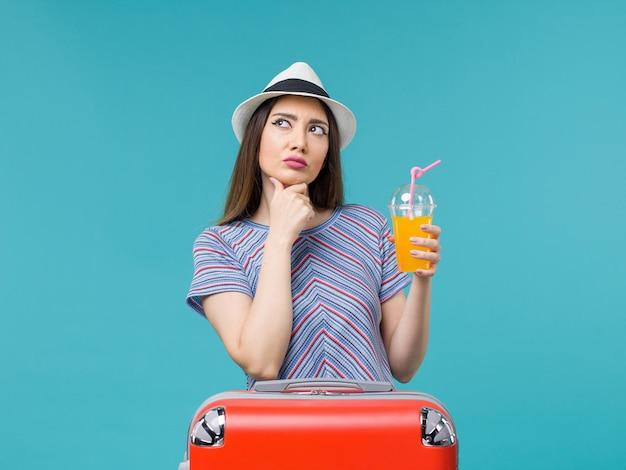 Donna di vista frontale in vacanza con la sua borsa rossa che tiene il suo succo sulla femmina di vacanza di viaggio viaggio viaggio sfondo blu