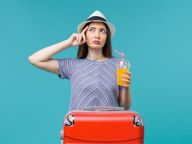 Donna di vista frontale in vacanza con la sua borsa rossa che tiene il suo succo sulla vacanza di viaggio viaggio viaggio estate mare sfondo blu
