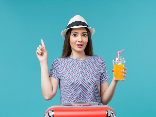 Donna di vista frontale in vacanza con la sua borsa rossa che tiene il suo succo sul viaggio femminile di vacanza di viaggio di viaggio dello scrittorio blu